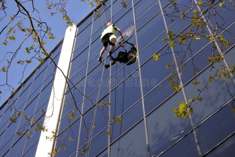 Le travailleur ayant beaucoup d'étages de nettoyage de vitres nettoie un immeuble de bureaux image libre de droits