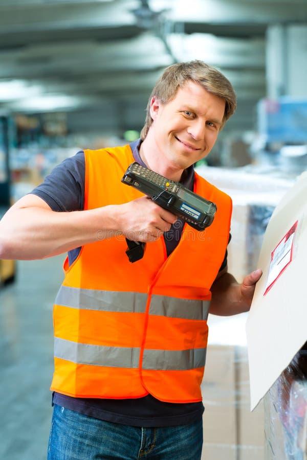 Le travailleur balaye le paquet dans l'entrepôt de l'expédition photographie stock libre de droits