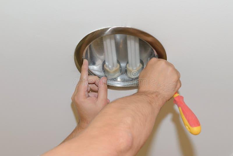 Le travailleur change l'ampoule dans le plafond du plafond photographie stock