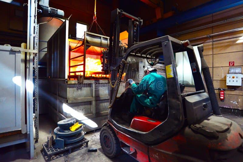 Le travailleur conduit le chariot élévateur à durcir le haut fourneau avec les composants en acier rougeoyants photo libre de droits