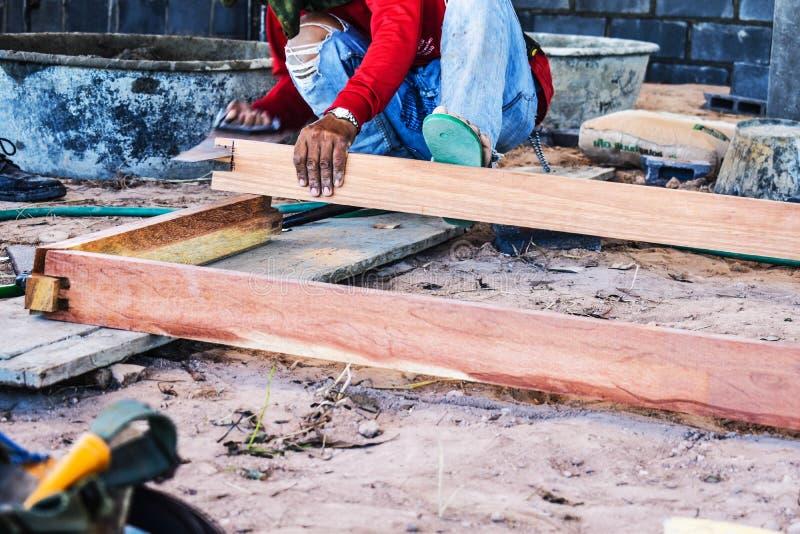 Le travailleur coupant le bois de construction par le manuel a vu l'outil au chantier de construction photo stock