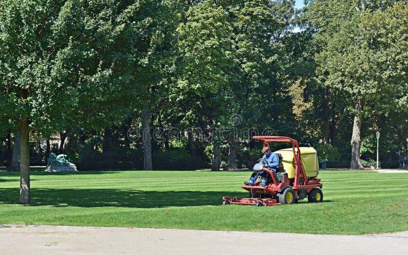 Le travailleur coupe l'herbe dans Cinquantenaire Parc à Bruxelles image stock