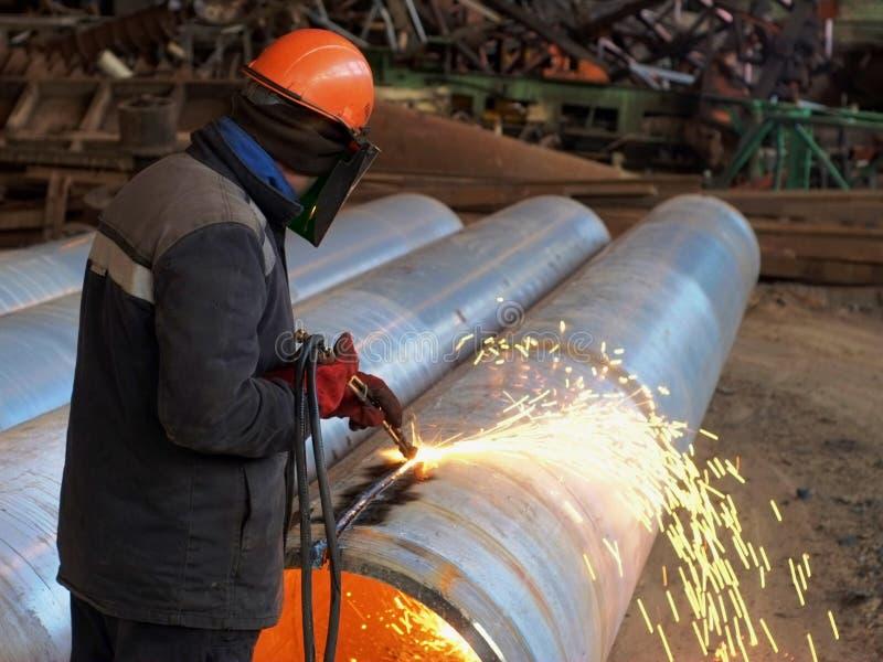 Le travailleur coupe le tuyau avec un coupeur de gaz photos libres de droits