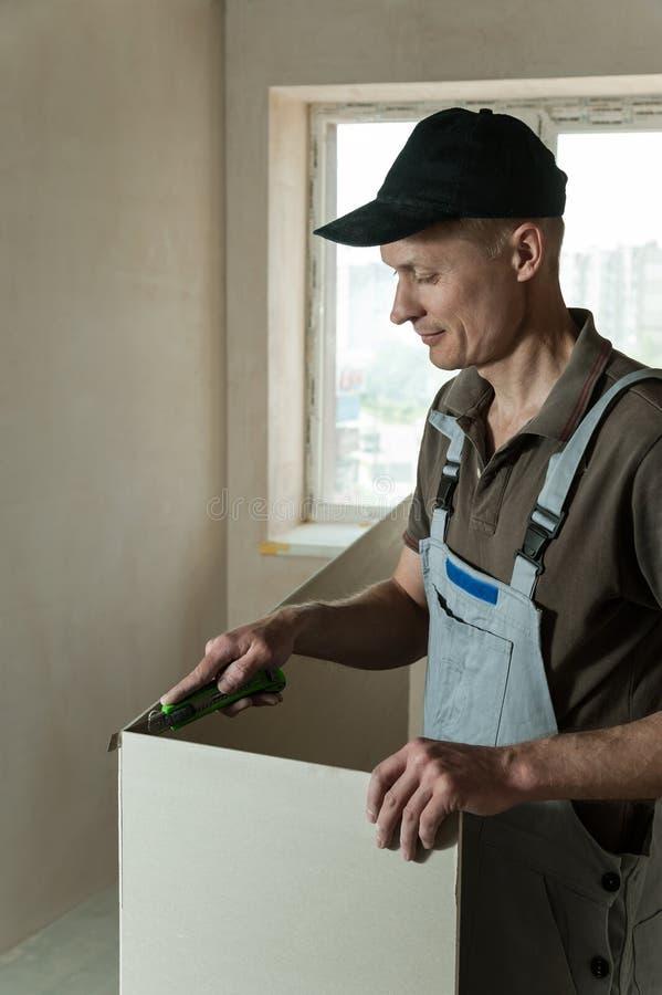 Le travailleur coupe un morceau de cloison sèche photo stock