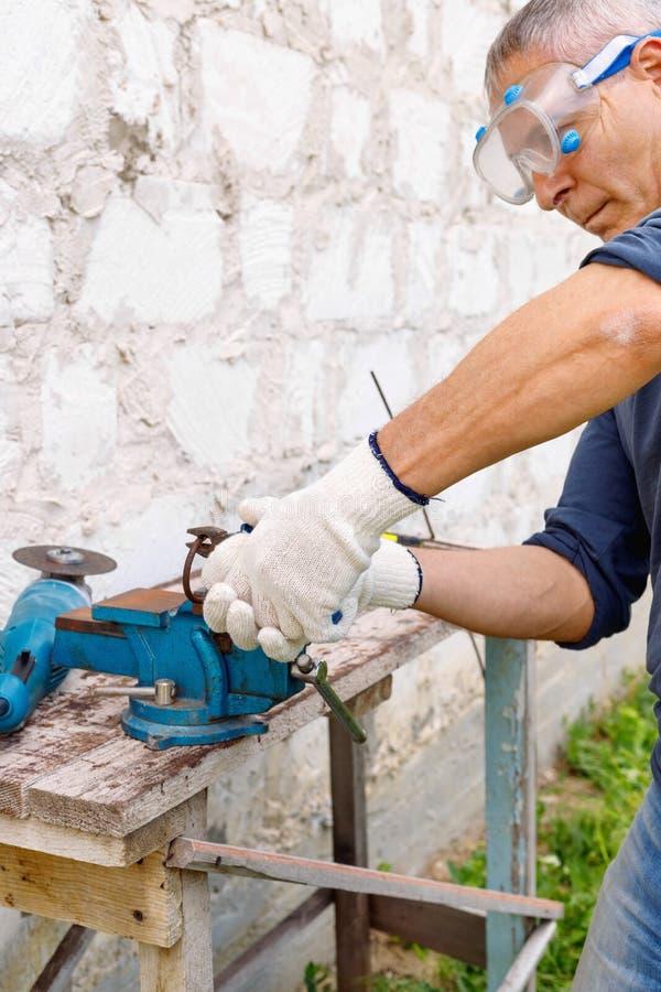 Le travailleur dépanne avec les outils électriques martèlent et des pinces dans l'arrière-cour de la maison dans extérieur image libre de droits