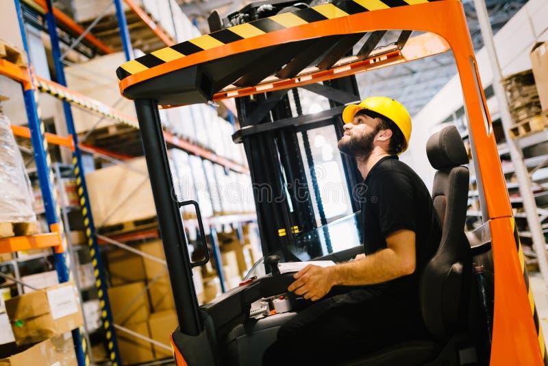 Le travailleur d'entrepôt faisant la logistique travaillent avec le chargeur de chariot élévateur photos libres de droits