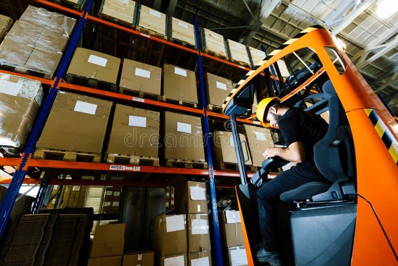 Le travailleur d'entrepôt faisant la logistique travaillent avec le chargeur de chariot élévateur photo stock