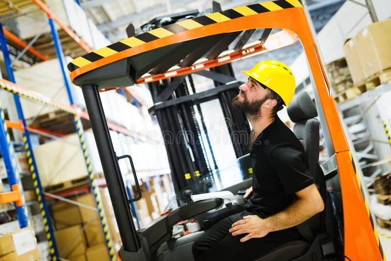 Le travailleur d'entrepôt faisant la logistique travaillent avec le chargeur de chariot élévateur photos stock