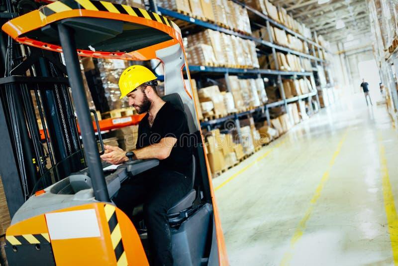 Le travailleur d'entrepôt faisant la logistique travaillent avec le chargeur de chariot élévateur photographie stock libre de droits
