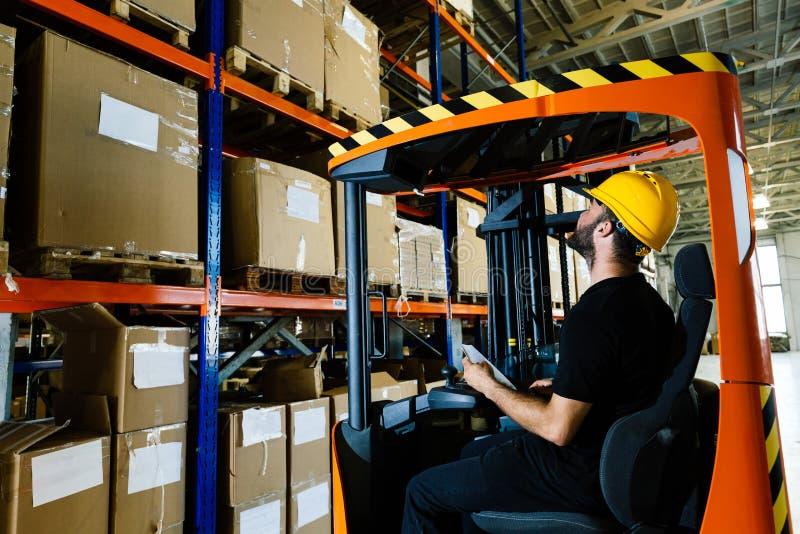 Le travailleur d'entrepôt faisant la logistique travaillent avec le chargeur de chariot élévateur image libre de droits