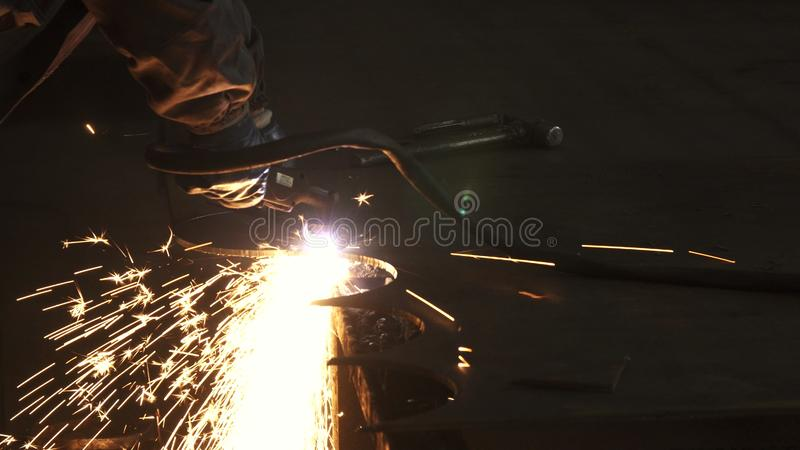 Le travailleur d'industrie dans la coupe uniforme protectrice metal manuellement photo stock