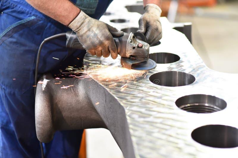 Le travailleur d'industrie mécanique rectifie le métal avec la machine pendant le c image libre de droits
