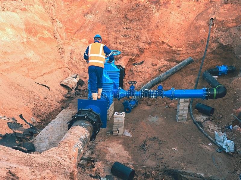 Le travailleur dans des vêtements de sécurité conduisent le conduit de valve sur la conduite d'eau potable de ville photographie stock