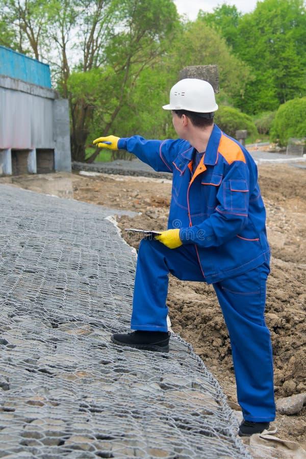 Le travailleur dans l'uniforme bleu, enregistre la construction d'un nouveau paysage et montre la quantité de travail photos libres de droits