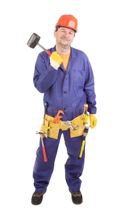 Le travailleur dans le casque antichoc tient le marteau photos stock