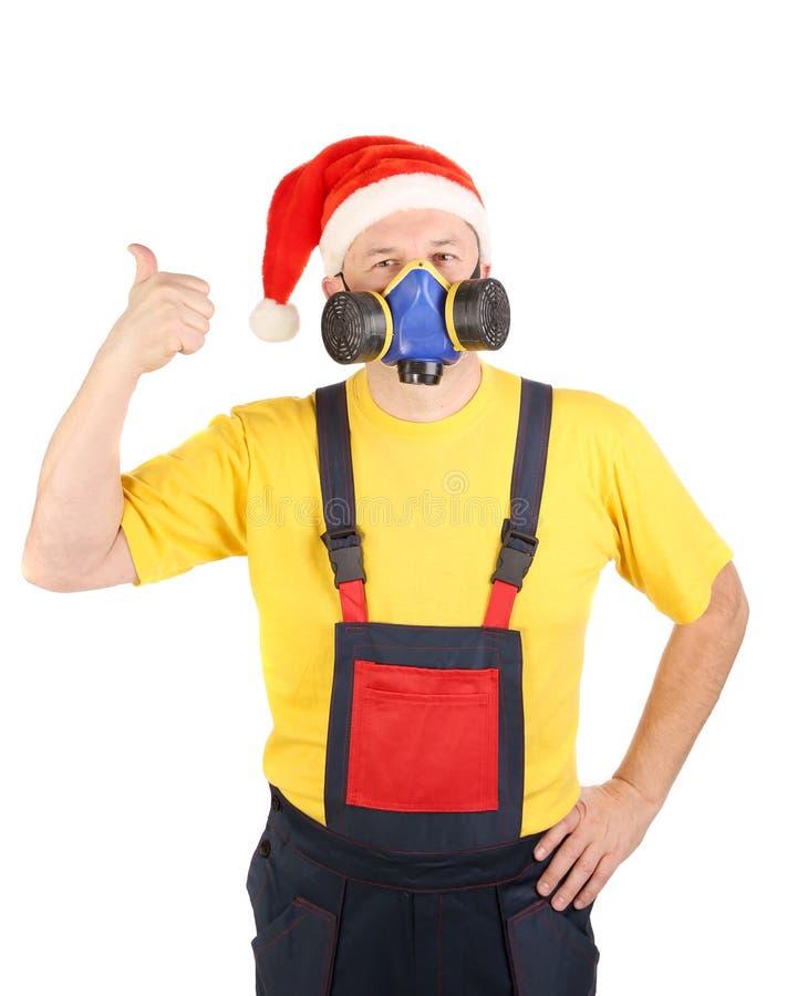Le travailleur dans le masque de gaz et le chapeau de Santa montre le pouce photo stock