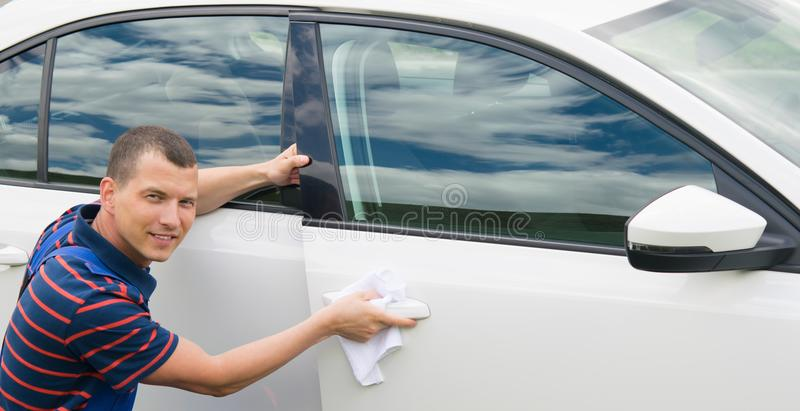 Le travailleur dans un costume bleu sourit et essuie la voiture avec du chiffon blanc photo libre de droits