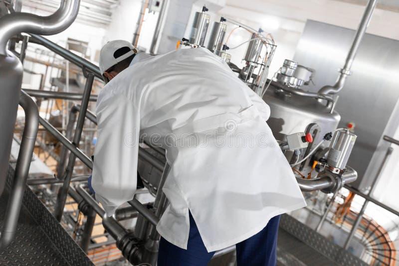 Le travailleur dans une robe longue bleue et un chapeau inspectent le d?partement de production de l'usine de laiterie photos stock