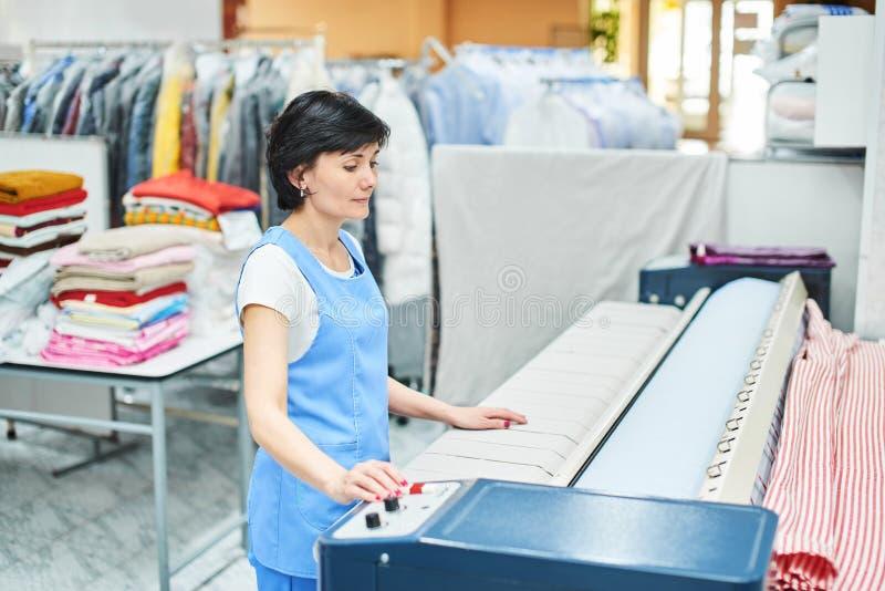 Le travailleur de blanchisserie de femme tapote la toile sur la machine automatique photos stock