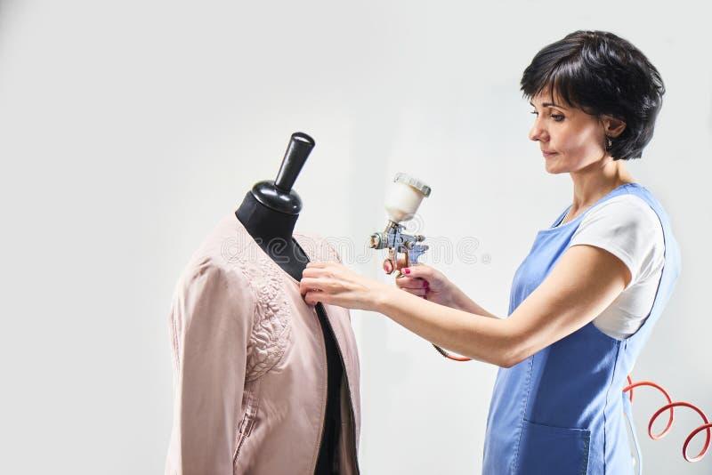 Le travailleur de blanchisserie de fille exécute les vestes en cuir de peinture sur un mannequin images libres de droits