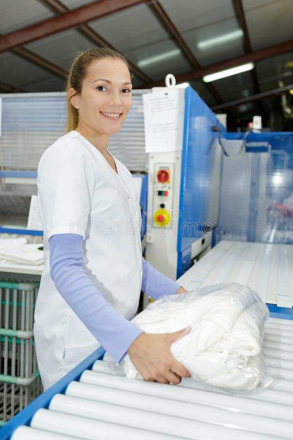 Le travailleur de blanchisserie met le textile repassé dans la machine repassante image stock