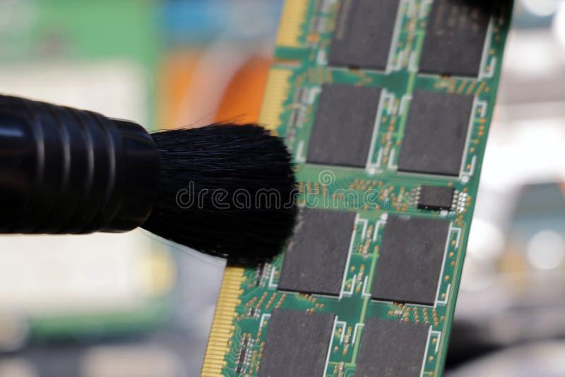 Le travailleur de centre de service nettoie la mémoire d'accès ou le panneau électronique RAM de la poussière au hasard photos stock