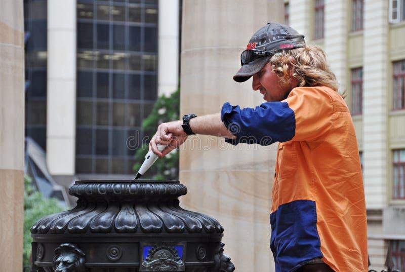 Le travailleur de conseil municipal de Brisbane allume la flamme éternelle de Remebrance images libres de droits