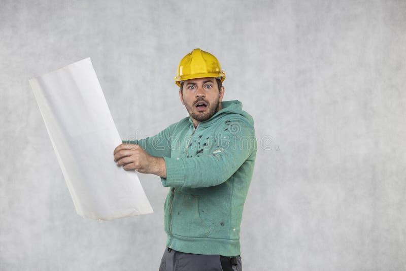 Le travailleur de la construction étonné passe en revue des plans de construction images stock