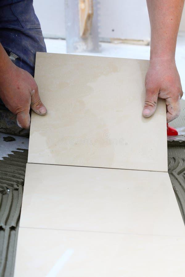 Le travailleur de la construction couvre de tuiles à la maison, adhésif de plancher de tuiles image libre de droits