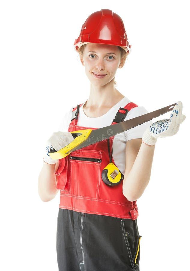 Le travailleur de la construction dans l'uniforme avec a vu photographie stock libre de droits