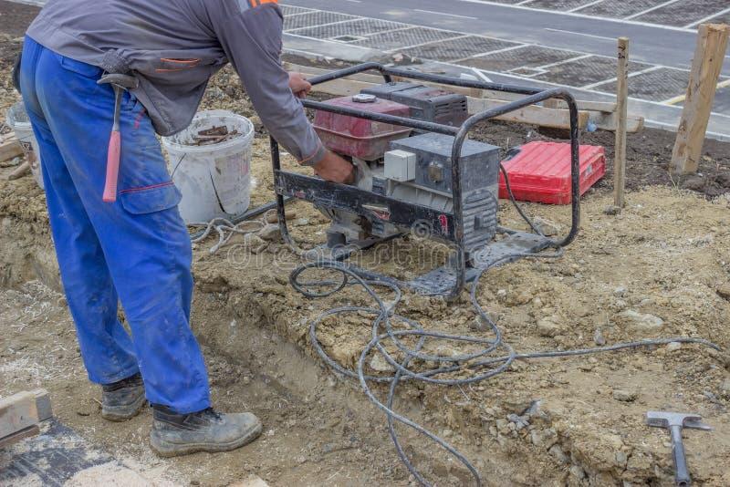 Le travailleur de la construction met en marche le générateur électrique portatif 2 photos stock