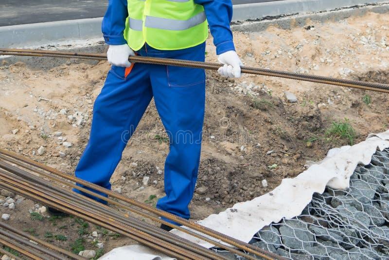 Le travailleur de la construction porte des tiges de fer, vue inférieure photo libre de droits
