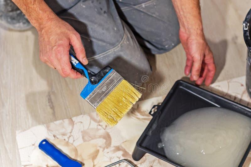 Le travailleur de la construction prépare la colle pour le papier peint photos libres de droits
