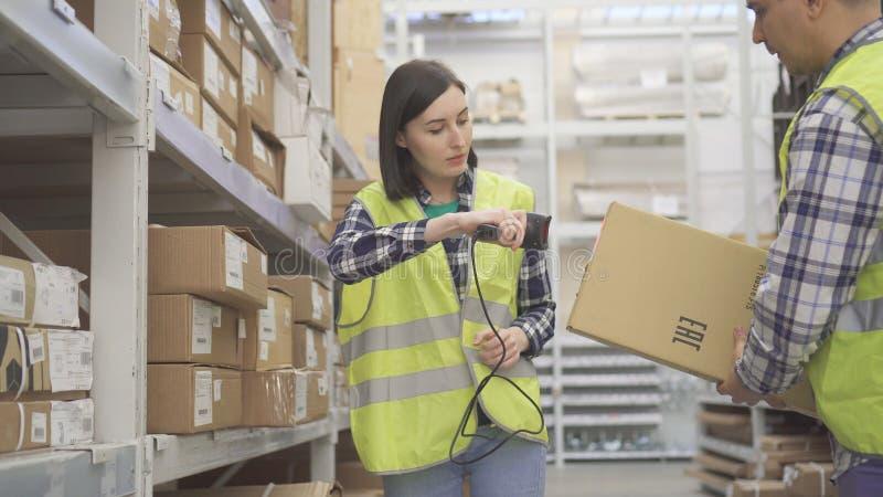 Le travailleur de magasin de femme balaye le scanner de code barres de produit images libres de droits