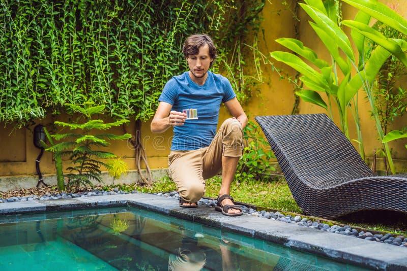 Le travailleur de piscine examine la piscine pour assurer la s?curit? Mesure de chlore et pH d'une piscine photographie stock