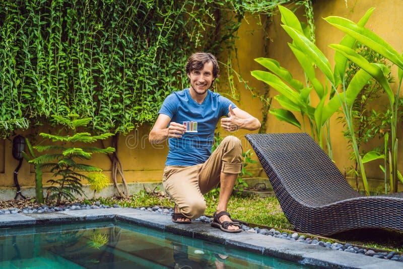 Le travailleur de piscine examine la piscine pour assurer la s?curit? Mesure de chlore et pH d'une piscine photos stock