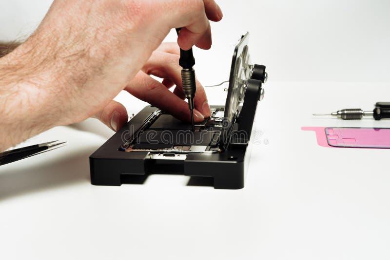 Le travailleur de réparation assemblent le smartphone cassé défectueux photographie stock