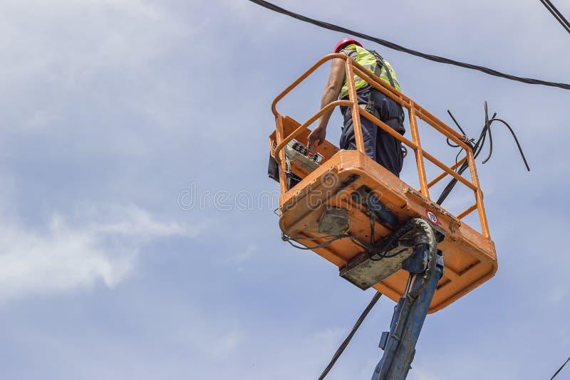 Le travailleur de service fixe la ligne électrique image libre de droits