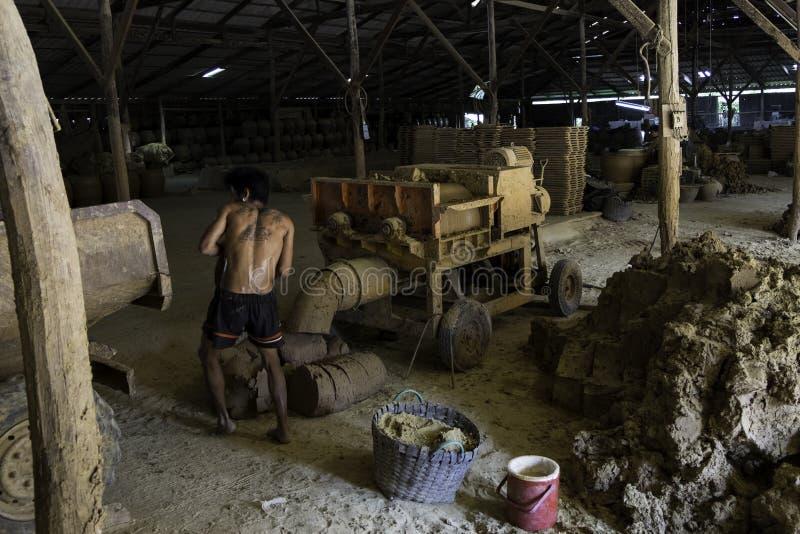 Le travailleur de sexe masculin prépare l'argile pour faire la poterie Une broyeur est employée pour préparer l'argile fin photographie stock libre de droits