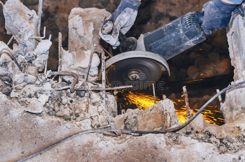 Le travailleur de sexe masculin scie le meulage de disque a vu l'armature dans un panneau concret renforcé, la destruction de la  image libre de droits