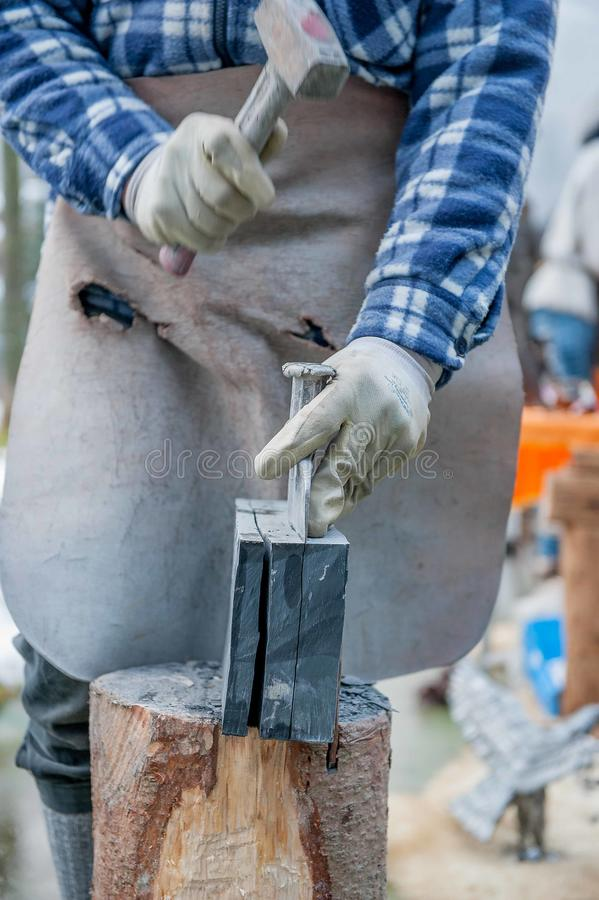Le travailleur divise la pierre avec le burin image stock