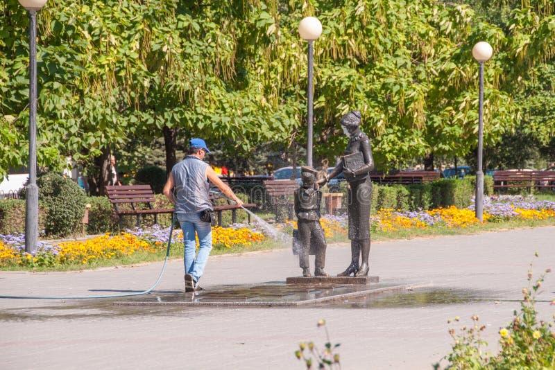 Le travailleur du logement et des services communaux lave avec de l'eau du monument de tuyau au premier professeur Volgograd image stock