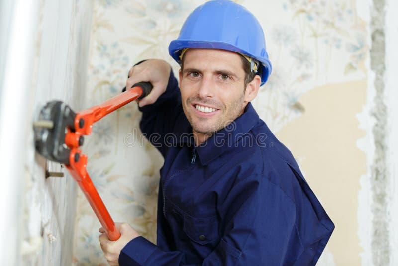 Le travailleur emploie des ciseaux sur le mur photographie stock