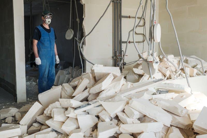 Le travailleur enlève des débris du mur détruit images stock