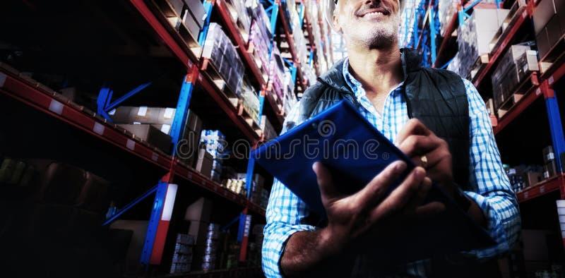 Le travailleur est souriant et tenant un presse-papiers dans un entrepôt images libres de droits