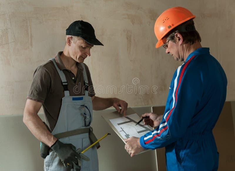 Le travailleur et l'agent de maîtrise discutent le plafond de plaque de plâtre de plan photographie stock
