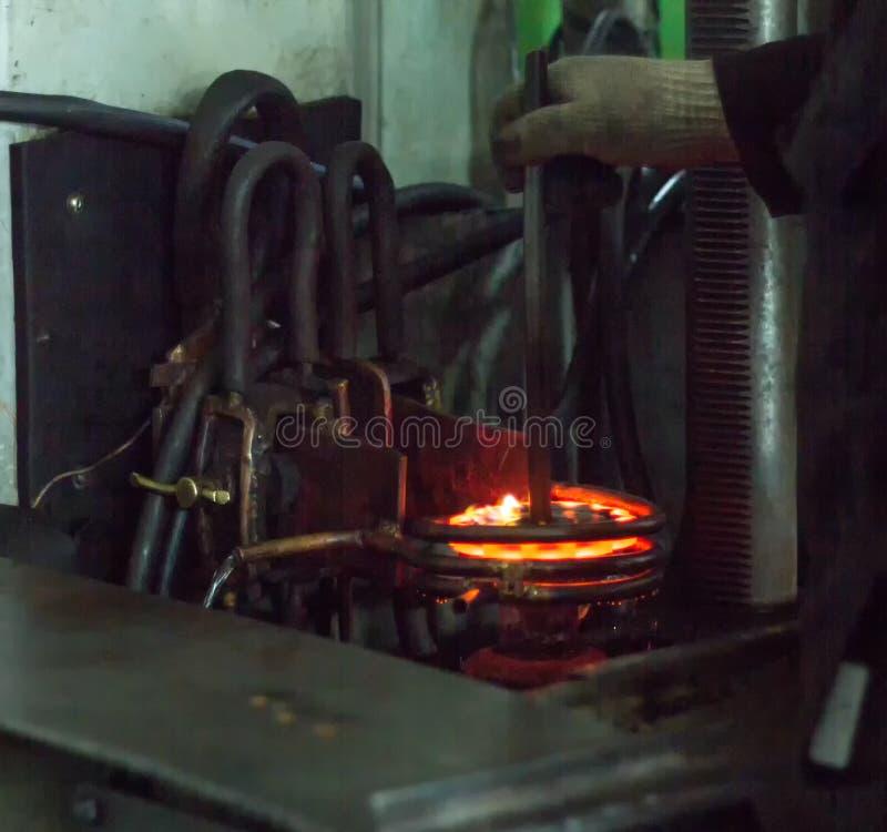 Le travailleur fait durcir le traitement thermique de la vitesse en métal sur une machine spéciale, le plan rapproché, durcisseme images stock