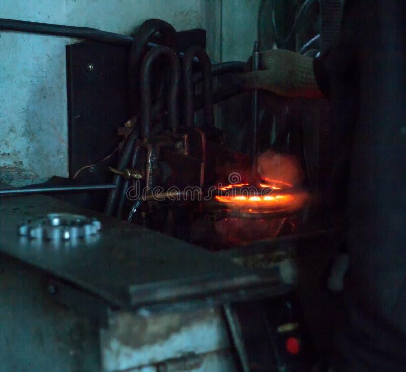 Le travailleur fait durcir le traitement thermique de la vitesse en métal sur une machine spéciale, le plan rapproché, durcisseme image stock