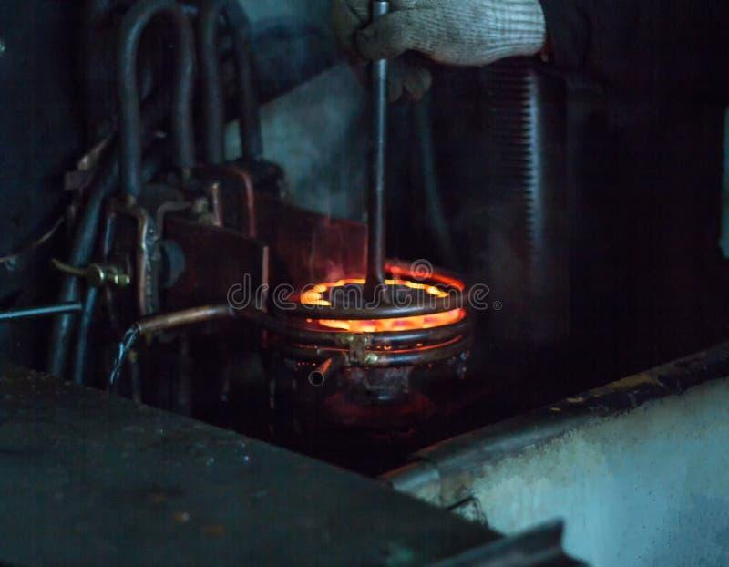 Le travailleur fait durcir le traitement thermique de la vitesse en métal sur une machine spéciale, le plan rapproché, durcisseme images libres de droits