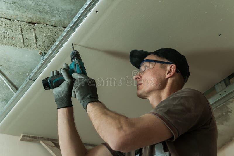 Le travailleur fixe la cloison sèche image libre de droits